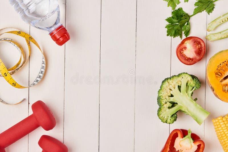 Groene paprika met het meten van band, domoren en fles water, stock foto