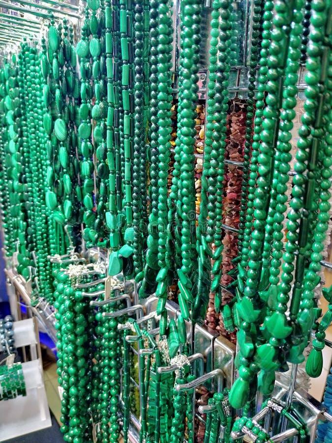 Groene parels die op de muur hangen Parels van verschillende vormen en types Gemaakt van natuursteen, turkoois stock fotografie