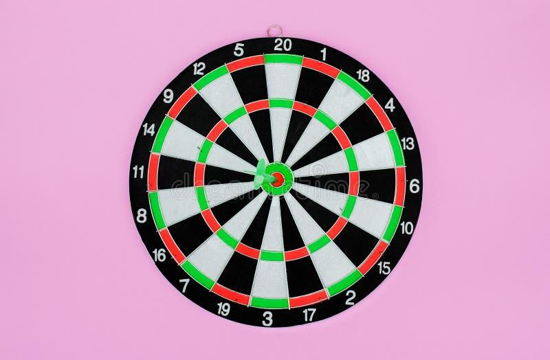 Groene pijltjepijl die in het doelcentrum raken van dartboard, metafoor aan doelsucces, winnaarconcept, op roze pastelkleurachter stock foto's