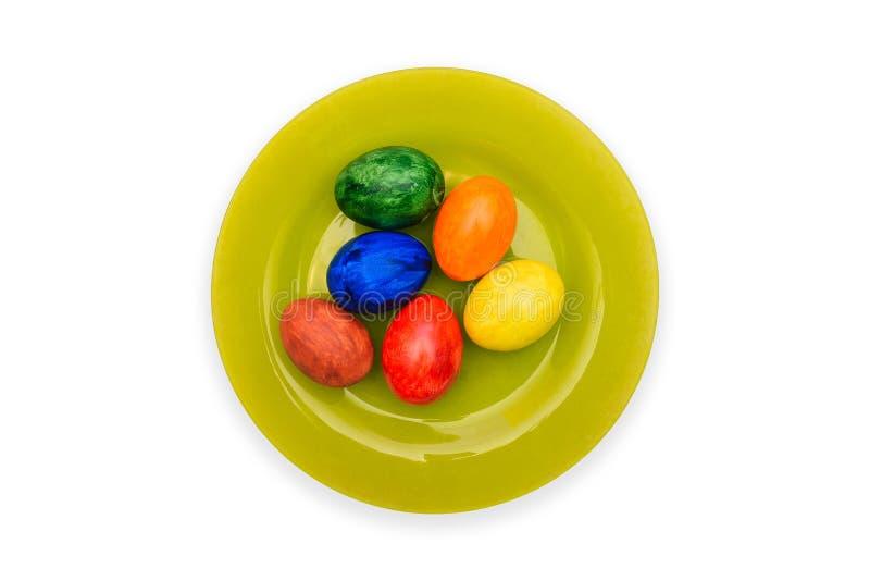 Groene plaat met eieren op een witte achtergrond Kleurrijke Paaseieren De Vakantie van Pasen royalty-vrije stock foto