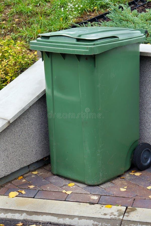 Groene plastic standaardhuisvuilcontainer die dichtbij vill wordt geïnstalleerd stock fotografie