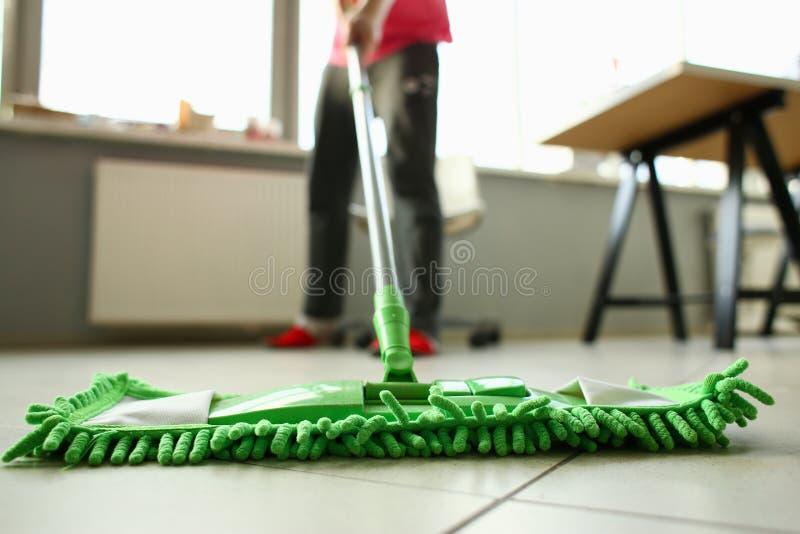 Groene plastic zwabber die gelamineerde lichte vuile vloer schoonmaken stock foto's