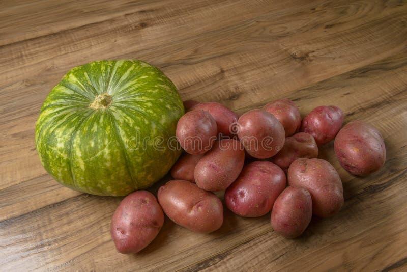 Groene Pompoen en Verse aardappels op Houten Lijst, Concept, Idee van Voedsel Rustieke Stijl stock foto's