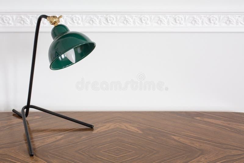 Groene retro lamp die zich op het houten uitstekende bureau voor witte lege muur met het vormen, exemplaarruimte bevinden stock afbeeldingen