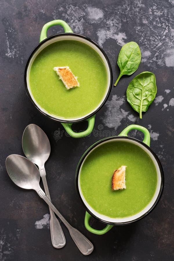 Groene room van spinaziesoep op een zwarte concrete achtergrond Vegetarisch voedsel Het concept het gezonde eten Mening van hierb stock foto
