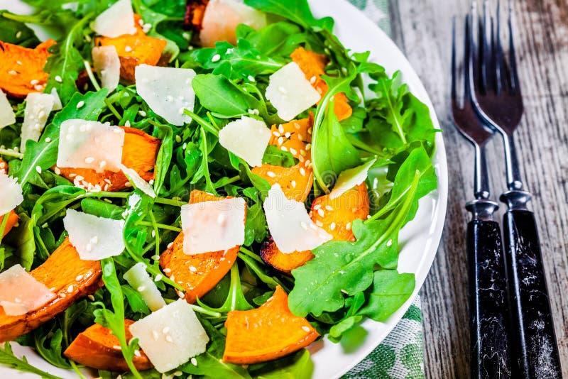 Groene salade met arugula, gebakken butternut pompoen, parmezaanse kaas en sesam stock fotografie
