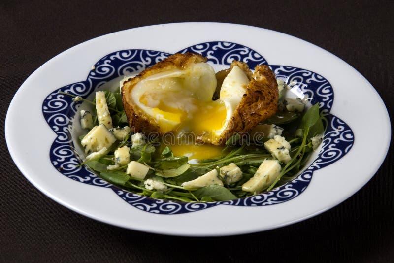 Groene salade met gebraden ei en kaas op een witte plaat royalty-vrije stock foto's