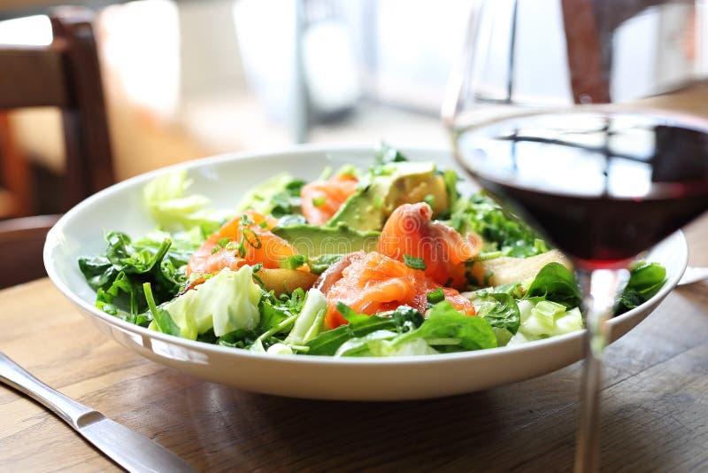 Groene salade met spinazie en raketbladeren met zalm, avocado en peer stock afbeelding