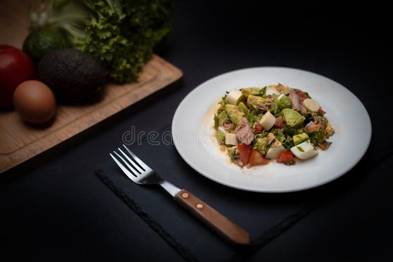 Groene Salade met tonijn op witte plaat over zwarte steenlijst stock afbeelding