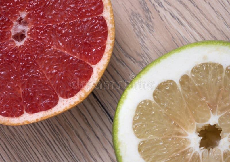 Groene Schat of Pomelit en Rode Grapefruit op houten achtergrond royalty-vrije stock foto's
