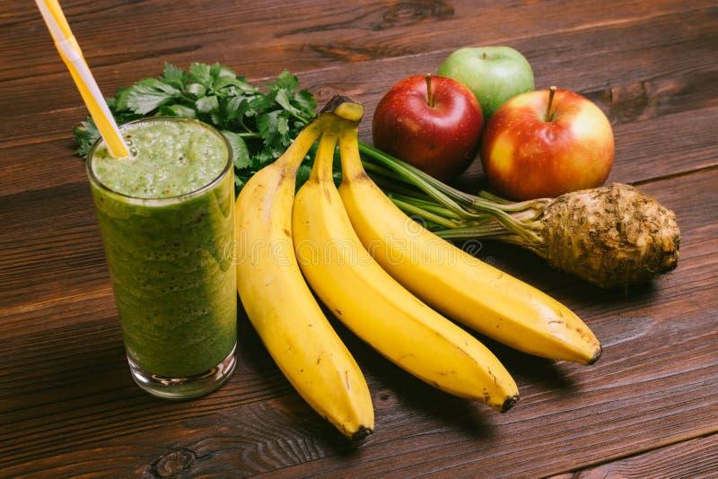 Groene smoothie in een glas met een stro, bananen, selderiewortel en stock foto