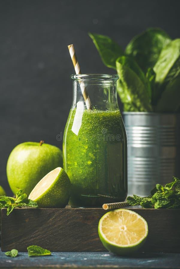 Groene smoothie in fles met appel, snijsla, kalk, munt stock foto's