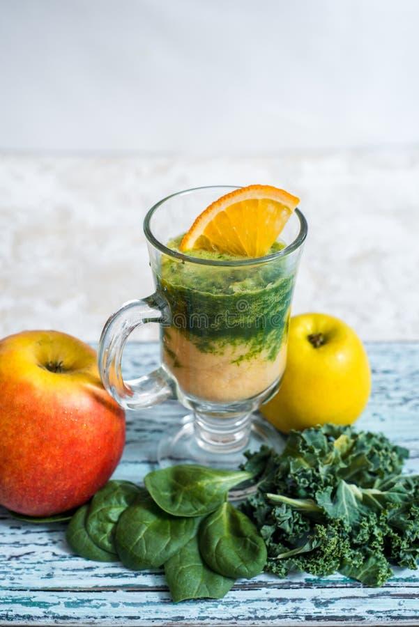 Groene smoothie maakte met spinazie, boerenkool, kiwi, groene appelen en bananen stock foto's