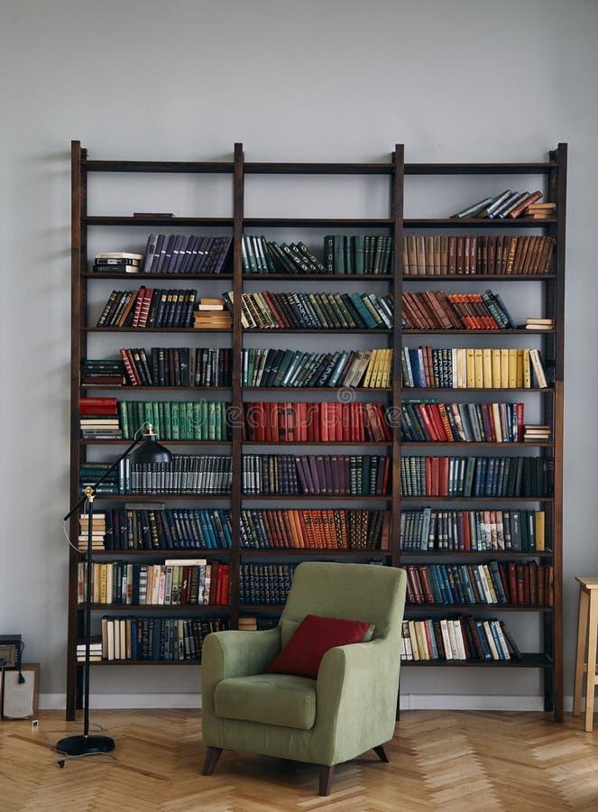 Groene stoel in het binnenland Boekenkast met oude boeken op de planken Boeken in een oud houten Kabinet stock foto
