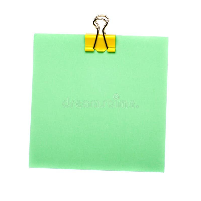 Groene Stoknota met gele die papercliphouder op witte achtergrond wordt geïsoleerd Spot omhoog stock foto's