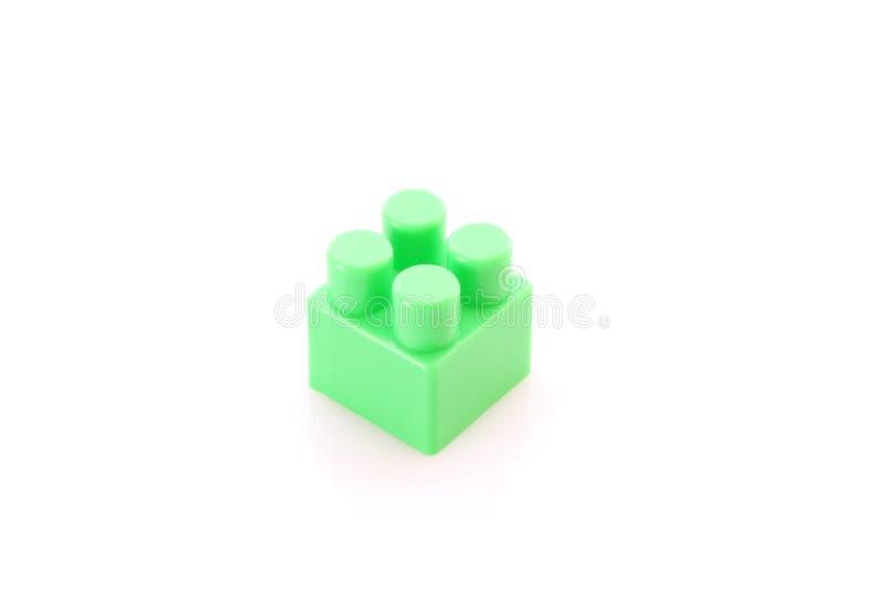 Groene stuk speelgoed geïsoleerded de bouwbaksteen royalty-vrije stock foto's