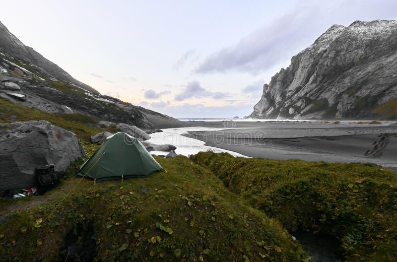 Groene tent die zich op een heuvel voor Bunes-Strand tijdens zonsondergang met bergen en de oceaan op de achtergrond op Lofoten b royalty-vrije stock foto