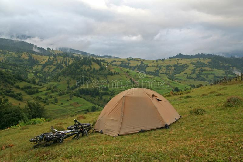 Groene tent en twee fietsen op een achtergrond van bergen stock foto