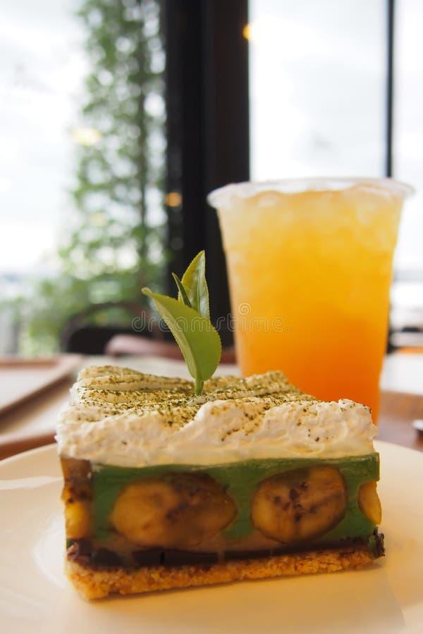 Groene Thee Banoffee, een prachtig verfraaide bakkerij op een witte plaat en de thee van het Citroenijs op de lijst in een bakker stock afbeeldingen