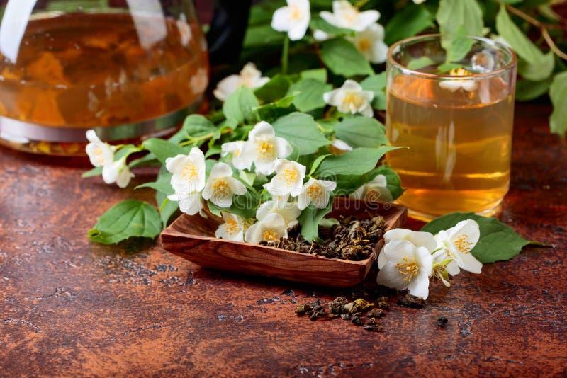 Groene thee met jasmijn in kop en theepot stock foto's