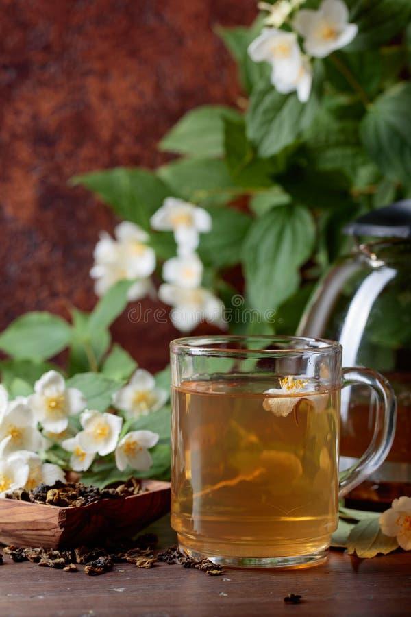 Groene thee met jasmijn in kop en theepot op houten lijst royalty-vrije stock afbeeldingen
