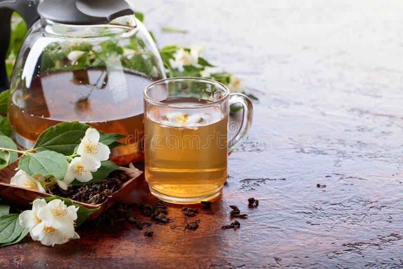 Groene thee met jasmijn in kop en theepot op oude koperlijst royalty-vrije stock fotografie