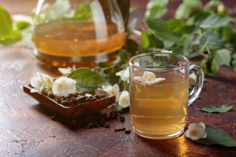 Groene thee met jasmijn in kop en theepot op oude koperlijst royalty-vrije stock afbeeldingen