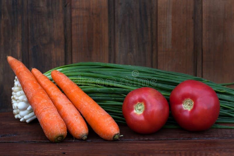 Groene uien, gewassen wortelen, rode tomaten royalty-vrije stock afbeelding
