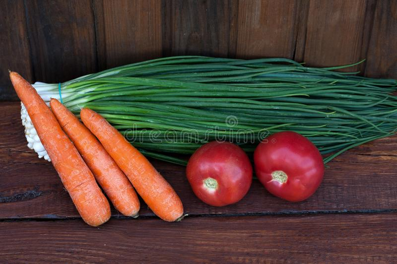 Groene uien, gewassen wortelen, rode tomaten stock foto