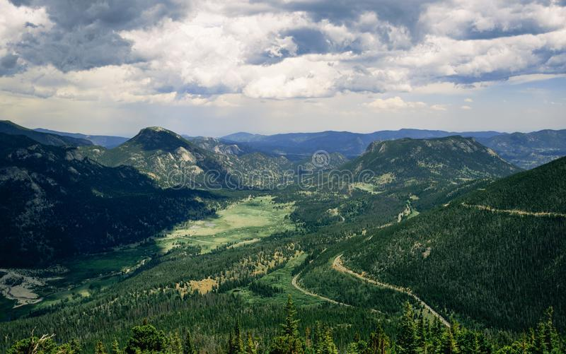 Groene vallei onder de pieken van Rocky Mountains royalty-vrije stock afbeeldingen
