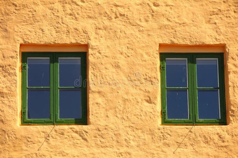 Groene vensters op oranje muur royalty-vrije stock foto
