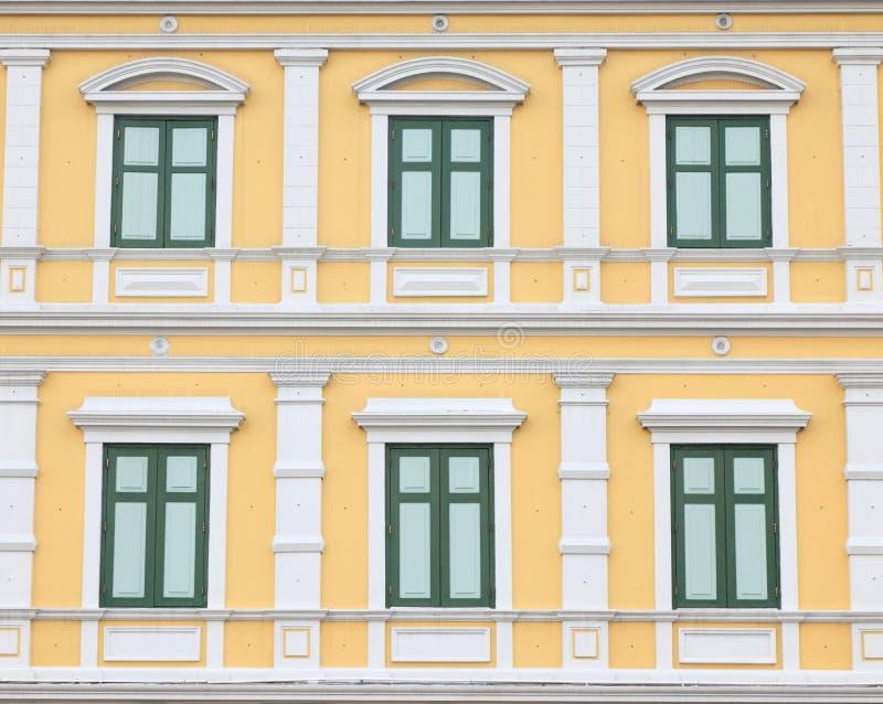 Groene vensters op oranje muur stock foto's