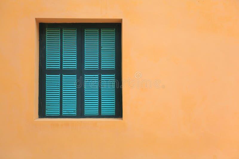 Groene vensters op oranje muur royalty-vrije stock fotografie