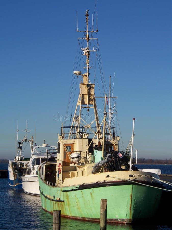 Groene vissersboot in haven stock afbeelding