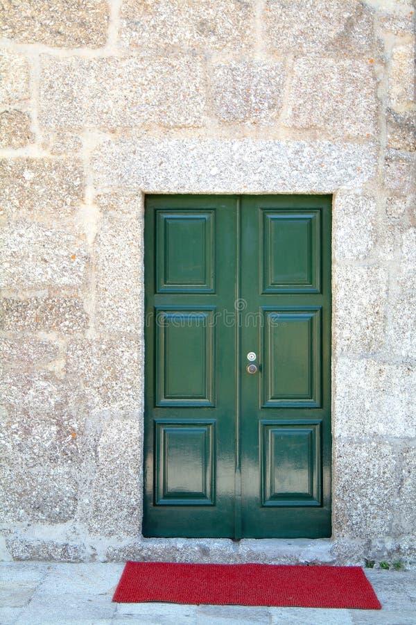 Groene voordeur en rood tapijt stock afbeeldingen