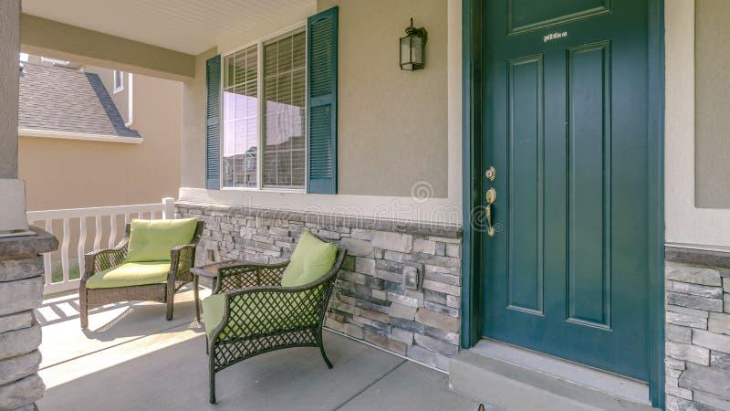 Groene voordeur met twee leunstoelen op de portiek stock afbeeldingen
