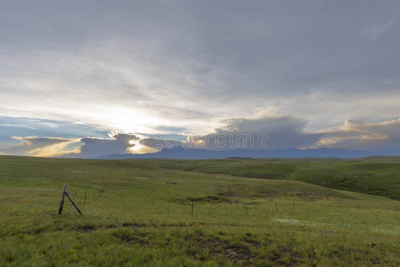 Groene weilanden en gele zonsondergang door wolken stock foto