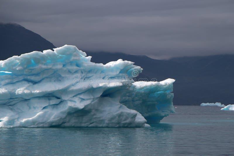 Groenland, blauwe ijsberg met lichtblauwe vlekken binnen van het andwith dramatische stemming van de hemel in de Atlantische Ocea royalty-vrije stock afbeeldingen