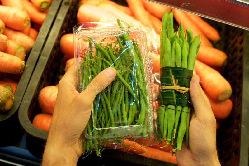 Groente die in banaanbladeren wordt verpakt versus Plastic verpakking stock afbeelding