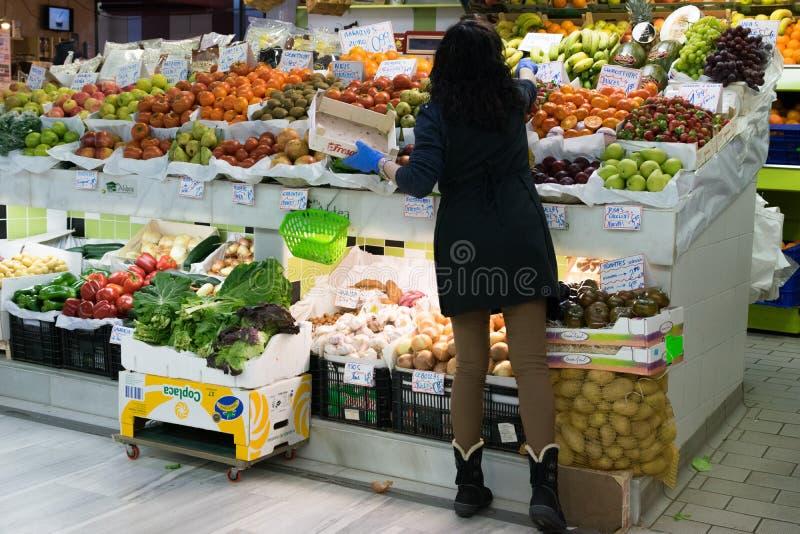 Groentehandelaar die fruit en groenten organiseren bij de markt stock fotografie