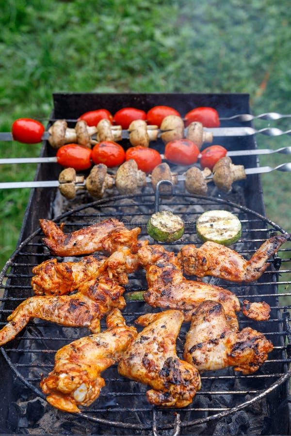Groenten en geroosterde kippenvleugels tomaten, paddestoelen en courgette Kip op open brand De partij van de de zomerbarbecue stock afbeeldingen