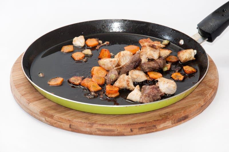 Groenten en vlees in een pan worden gebraden die royalty-vrije stock foto's