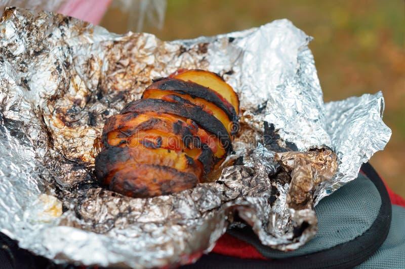 Groenten in folie op brand, aardappelen in de schil worden gebakken die stock afbeelding