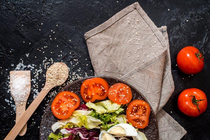 Groenten op de zwarte achtergrond Organisch voedsel en verse groenten Komkommer, kool, peper, salade, wortel, broccoli, royalty-vrije stock afbeeldingen