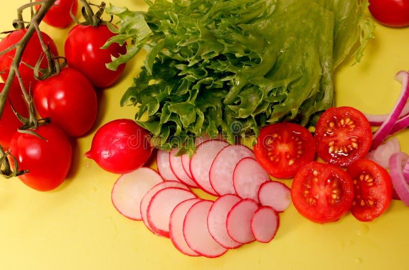 Groenten zoals radijs, tomaat en sla op gele achtergrond stock afbeelding