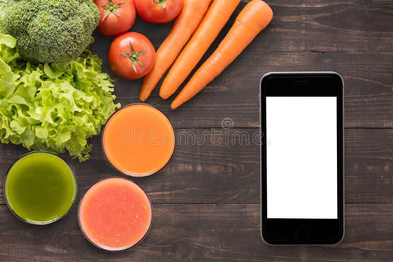 Groentesappen en smoothie op houten achtergrond met smartpho royalty-vrije stock foto
