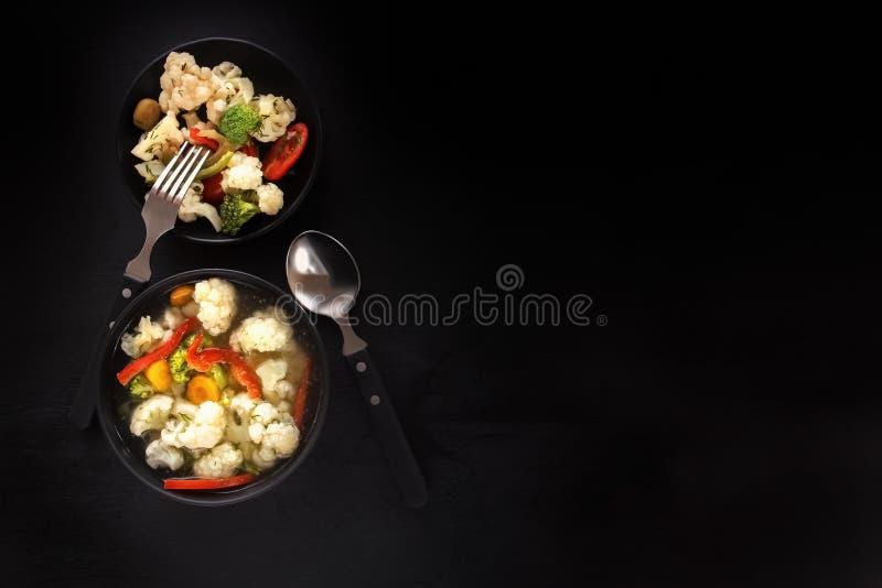 Groentesoep en salade van bloemkool, wortelen, tomaat, peper en kruiden in een zwarte plaat op een zwarte achtergrond stock foto