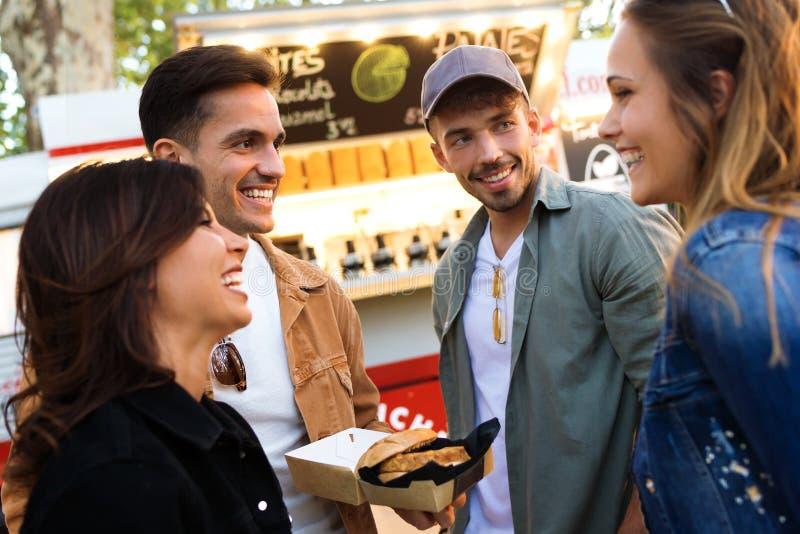Groep aantrekkelijke jonge vrienden die terwijl het bezoeken markt in de straat eet spreken royalty-vrije stock afbeeldingen