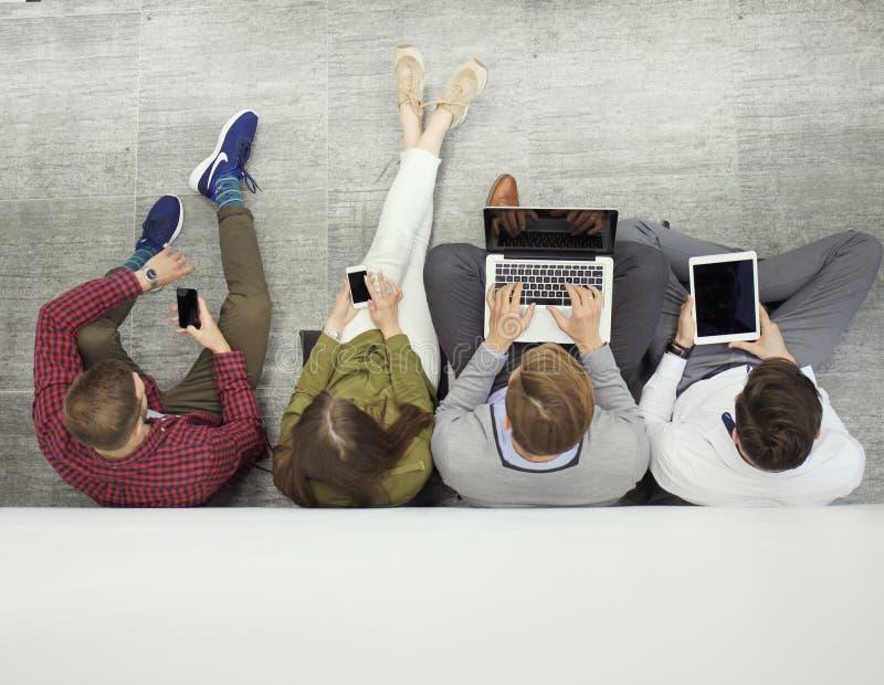 Groep aantrekkelijke jongeren die op de vloer zitten die laptop, Tabletpc, slimme telefoons, het glimlachen met behulp van stock foto