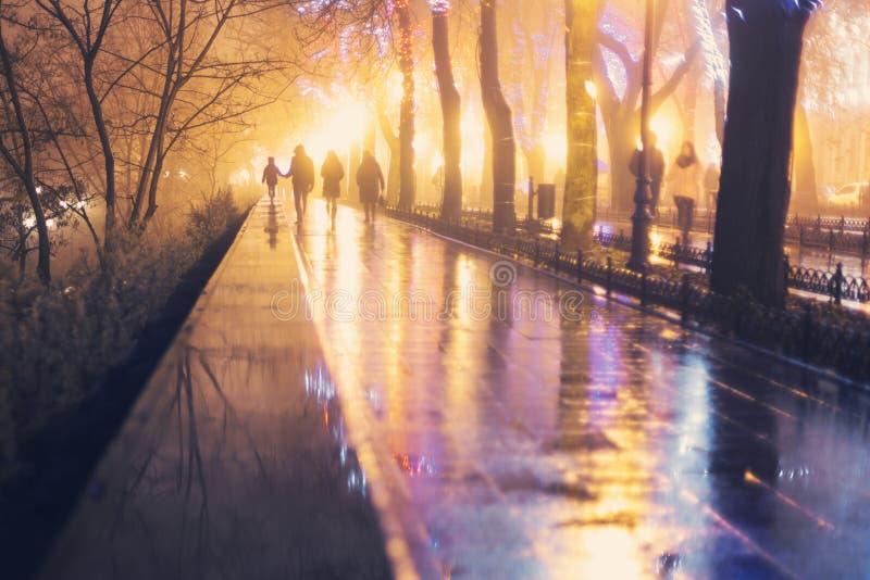 Groep abstracte mensen die onderaan de regenachtige boulevard lopen royalty-vrije stock foto's